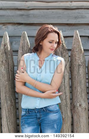 Beautiful girl on the background of a wooden fence.
