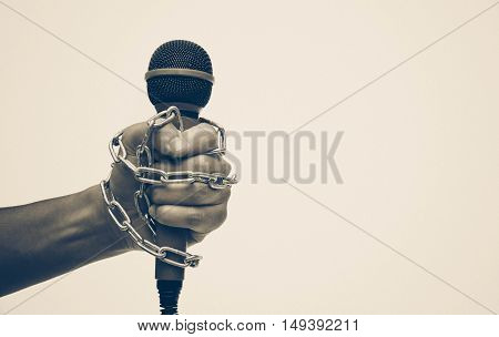 Hand holding a microphone with a chain - Freedom of the press is at risk concept - World press freedom day concept