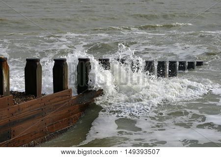 Waves crashing against a breakwater at Eastbourne in Sussex. Background of brown sea and small waves with a small area of shingle.
