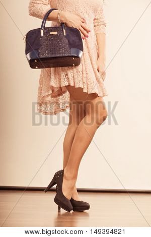 Fashion shoes concept. Beautiful lady in cute dress is holding black handbag. Woman is wearing high heels.