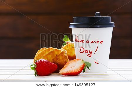 paper cup with hot coffee and a muffin for breakfast
