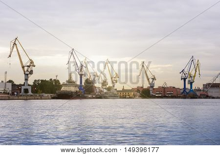 Sea port with cranes in sunlight in the evening.