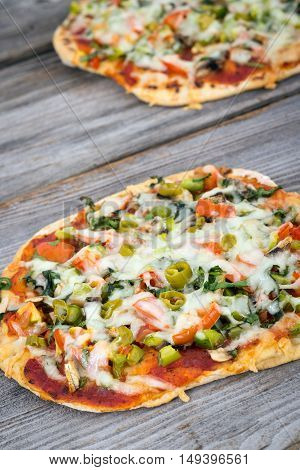 thin crust homemade pizza with vegetables on table