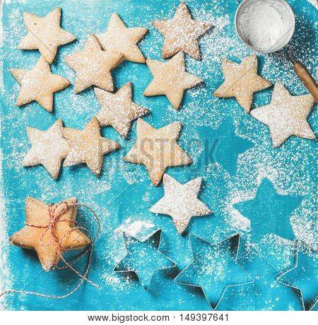 Christmas or New Year holiday food background. Sweet gingerbread cookies in shape of star with sugar powder and metal shapes on blue painted plywood background, top view