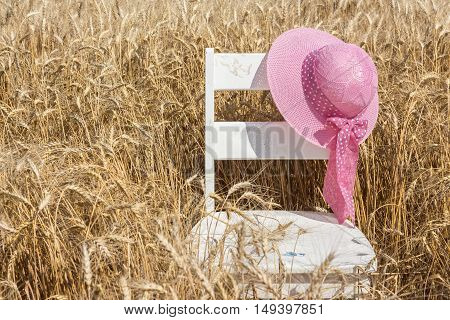 horizontal image of an old white chair sitting in a wheat field with a wide brimmed pink hat hanging over the back rest in the summer time