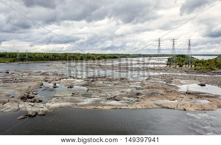 horizontal image of vastly receded lake close to an electricity dam with flat rock and shale exposed with electricity towers in the background under a very cloudy sky in the summer.