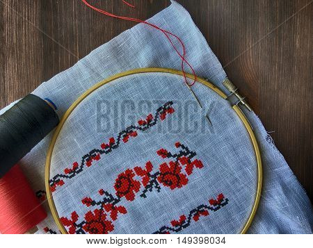 fabric in the wooden embroidery hoop with traditional folk embroidery Ukraine top view vintage toning