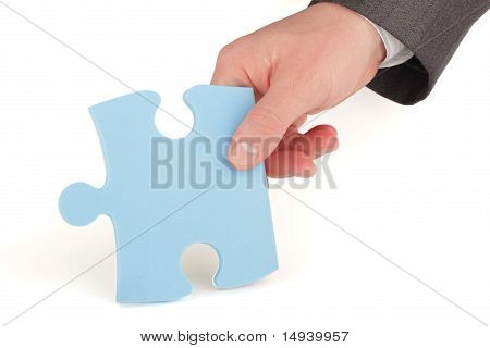 Businessman holding a piece of blue puzzle