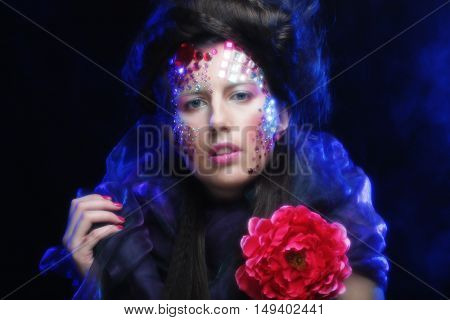 young woman with artistic visage holding big red flower