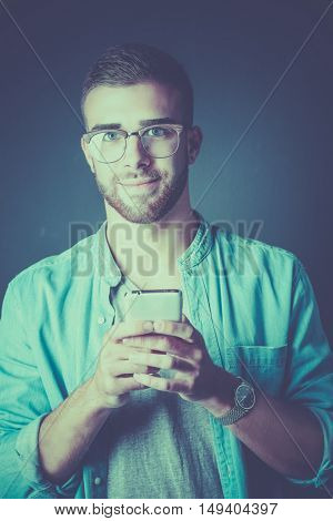 Smiling young man holding phone while text messaging
