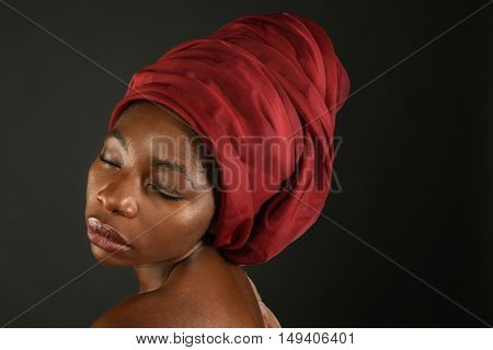 Portrait of African woman wearing red turban isolated over dark background