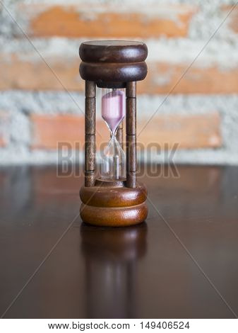 Closeup wooden hourglass stone background, select focus