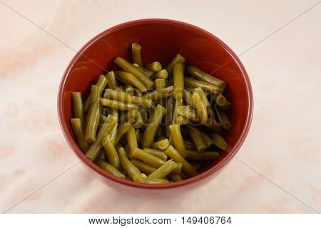 Canned green beans in red bowl on table covered by tablecloth