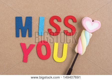 Words miss you with heart candy on brown background