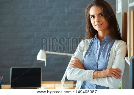 Young woman standing near desk with laptop