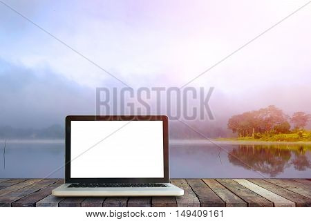 Laptop on wood floor perspective on the lake and forest backgrounds.Mock up for display or montage of productBusiness presentation