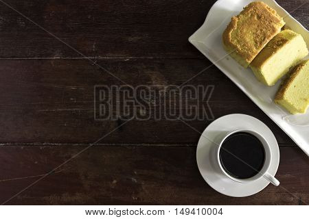 Coffee cup and saucer with cake on wooden table with copy space