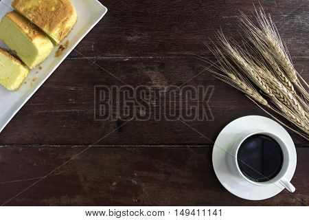 Coffee cup and saucer with wheat and cake on wooden table with copy space