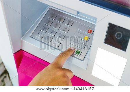 woman using ATM machine to withdraw money