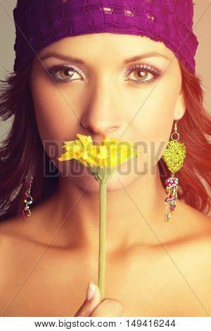 Beautiful woman smelling yellow flower