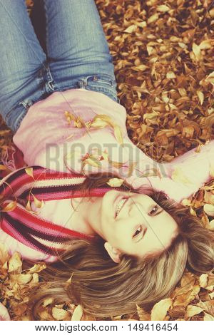 Beautiful woman playing in autumn leaves