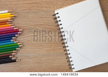 color pencils with a notebook on a wooden table