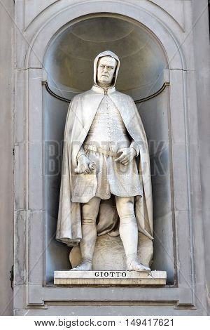 FLORENCE, ITALY - January 20, 2016: Giotto di Bondone ( italian painter and architect ) statue by Giovanni Dupre on facade of Uffizi Gallery, Florence, Italy