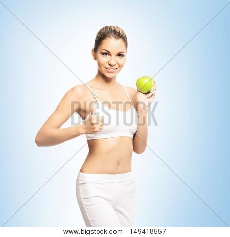 Sporty, athletic and attractive woman with apple over heaven background. Sport, dieting and healthy lifestyle concept.