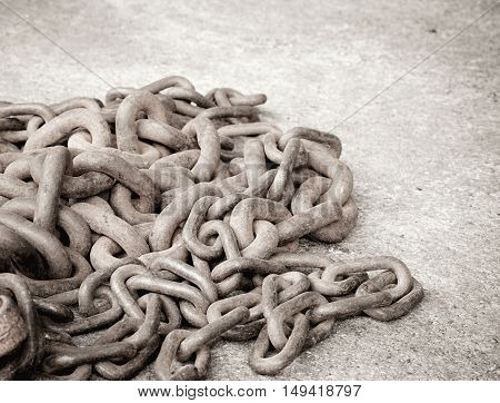 Group of old and rusty chain links on concrete floor background with color filter effect
