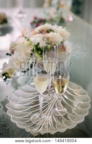 Two glasses of champagne on table and flower