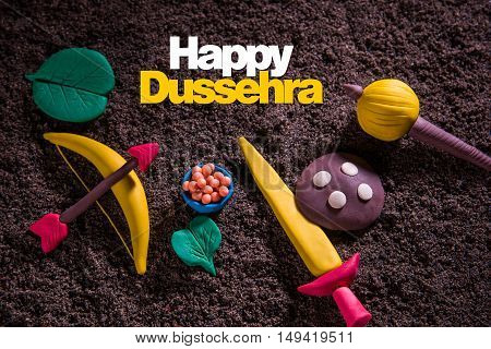 happy dussehra greeting card made using a photograph of colourful clay models of ancient indian armour used in Ramayana and Mahabharata like bow and arrow, sword and shield, gada or gadda, apta leaf