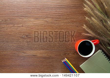 workspace with coffee pencils notebook and grass on wooden table