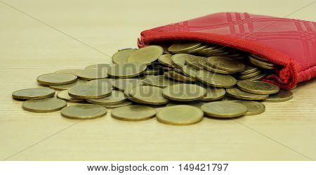 Gold Coins From Small Coin Leather Pocket On Wood Background