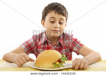Niño comiendo una hamburguesa grande