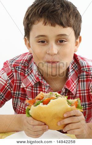 Menino comendo um hambúrguer grande