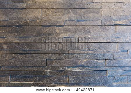 Block cut stone wall in gray color with warm and cool lights background