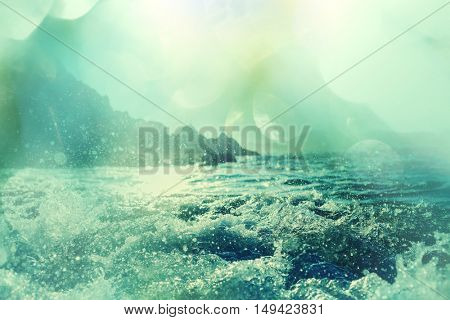 Blue wave on the beach. Blur background and sunlight spots. Peaceful natural background.