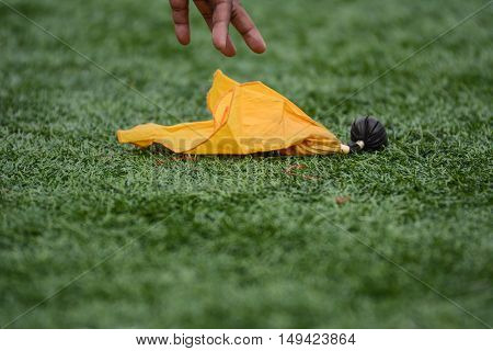Artificial Turf and Yellow Football Penalty Flag being Picked Up