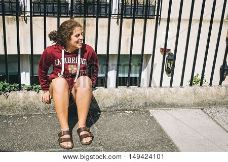 Bath UK - August 15 2015: Happy young casual woman sitting in the fence in a street.