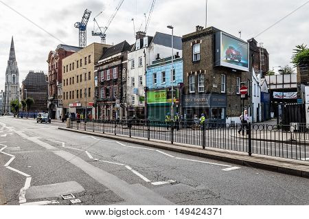 LONDON UK - AUGUST 25 2015: London street scene. Westminster Bridge Roadwith construction cranes ans retail stores on a overcast day