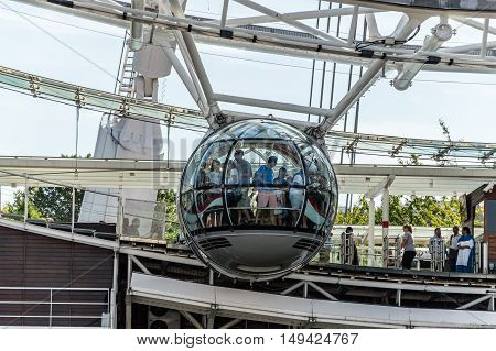 LONDON UK - AUGUST 23 2015: People getting on the glass cabins of London Eye. The London Eye is giant Ferris wheel on the South Bank of the River Thames in London. Also known as the Millennium Wheel.