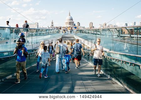 LONDON UK - AUGUST 22 2015: People walking over Millennium bridge a sunny day. St Pauls Cathedral in the background.