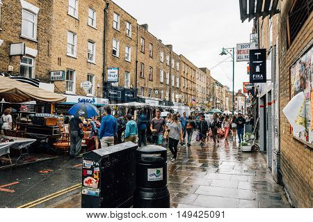 LONDON UK - AUGUST 23 2015: People at Brick Lane Market stalls a rainy day. Almost anything can be found on Brick Lane from antique books to trendy and fashion designs.