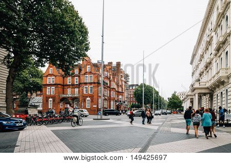 London UK - August 19 2015: People walking on Exhibition Road in London. It is a street in South Kensington London which is home to several major museums and academic establishments. Cloudy day.