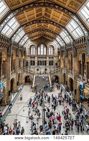 London UK - August 19 2015: Main hall of famous London Natural History Museum with tourists visitors. High angle view with a wide open lens