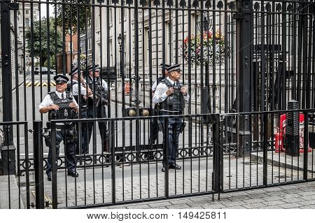 London UK - August 18 2015: Police officers protecting the gate of Downing street in London the residence of the prime minister.