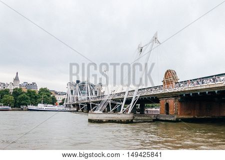 LONDON UK - AUGUST 22 2015: Hungerford Bridge and Golden Jubilee Bridges from the river at sunset