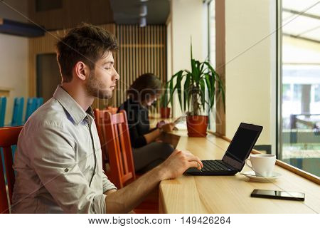 Morning in modern city, youth lifestyle. Young man looks on screen of laptop, work in public place, sitting indoor in urban cafe. Social networks, freelancer job concept.