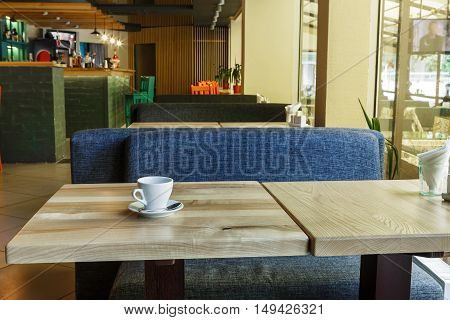 Table with coffee cup in modern restaurant or cafe interior. Public place interior design, bright red wooden chairs and blue sofas, large windows and bar. Morning light, nobody indoors.