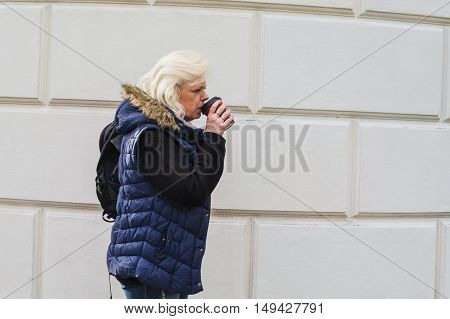 Side portrait of a blonde woman with a coffee to go.